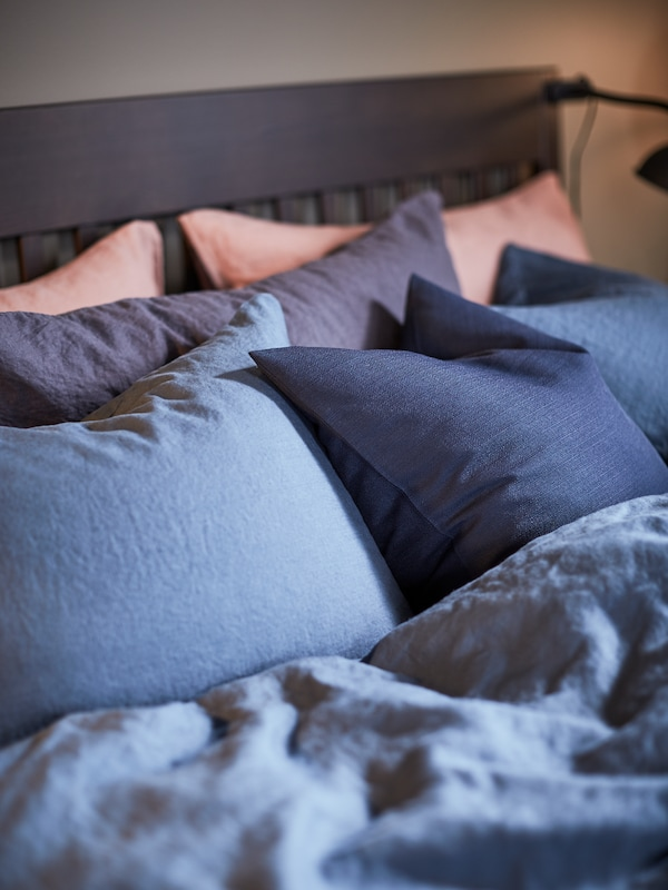 A close-up of an IDANÄS bedframe with a PUDERVIVA dark blue quilt cover and pillowcases.