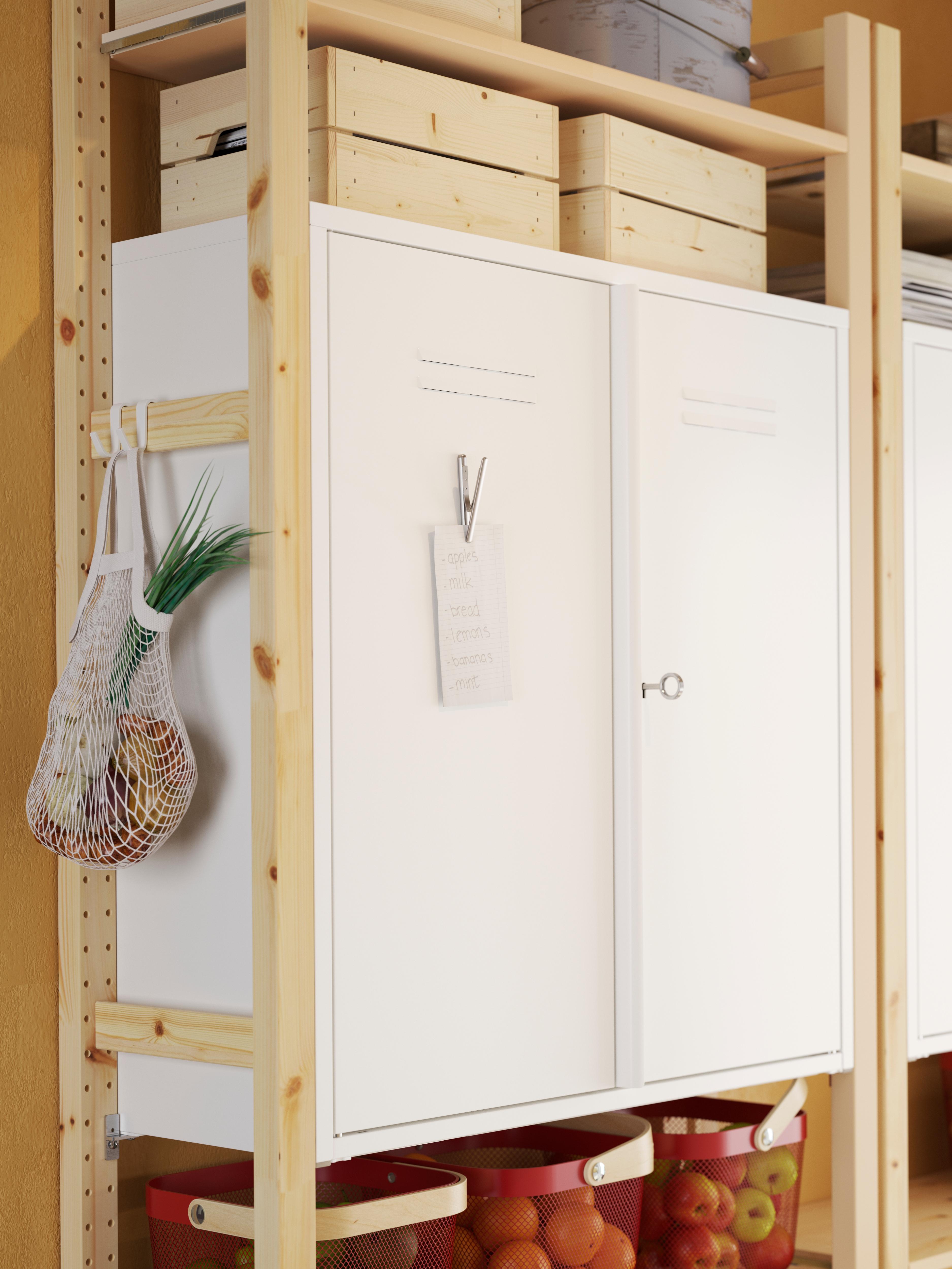 Secção de uma estante em pinho com um armário IVAR em metal branco, um clipe com uma mensagem na porta e um saco de rede com legumes pendurado num gancho.