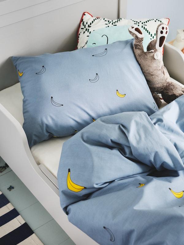 Pokój dziecięcy z szarym łóżkiem, pluszowym króliczkiem i niebieską pościelą VÄNKRETS z nadrukiem przedstawiającym banany.