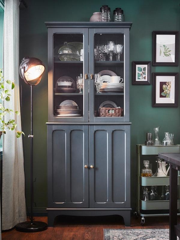 La vaisselle est rangée dans une armoire bleu-vert à portes vitrées. À côté, un lampadaire noir et une desserte gris-vert.