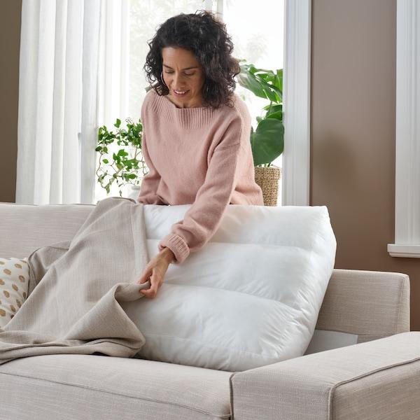 امرأة تقف خلف صوفا KIVIK بيج تقوم بتغيير غطاء إحدى وسائد الظهر.