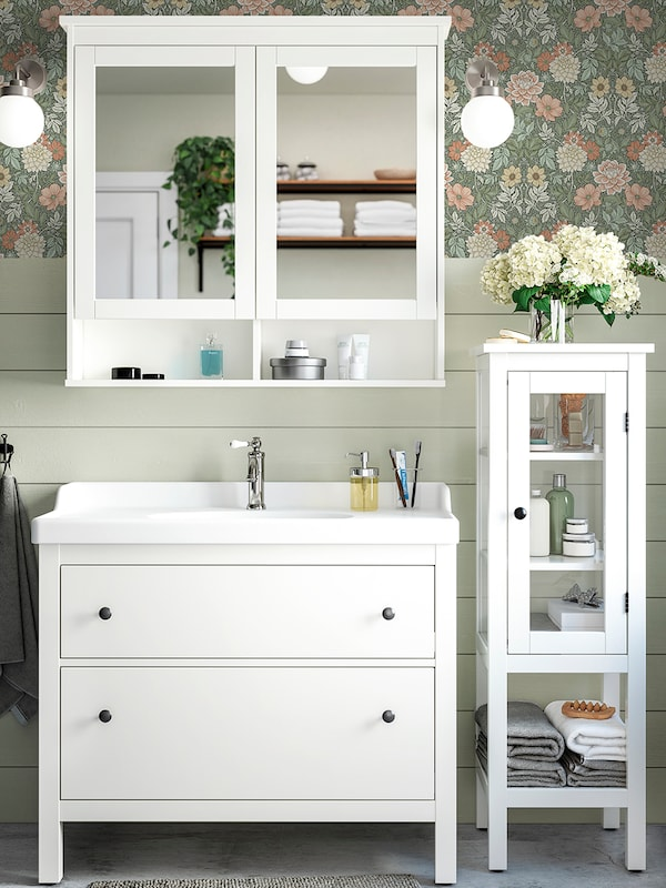 A white HEMNES mirror cabinet above a white wash-stand with two drawers, next to a high cabinet with a glass door.