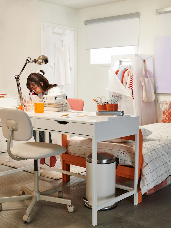Un birou alb, cu un scaun rotativ pe o parte și o studentă care stă în cealaltă parte, toate într-o cameră neobișnuită pentru studenți.