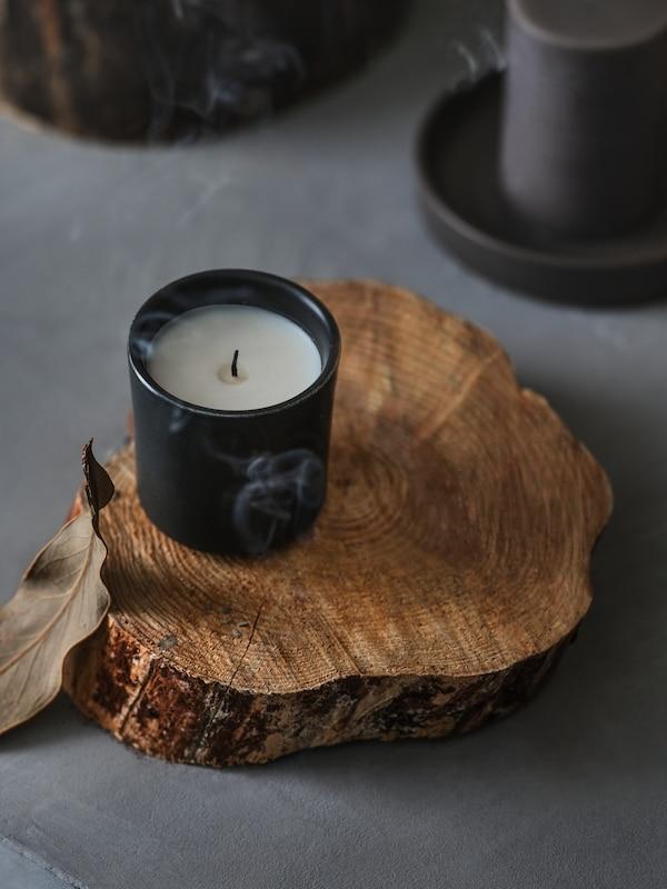 Ett BEHJÄRTAD doftljus i keramikkruka står på en grovhuggen träbit; en rökslinga sipprar runt.