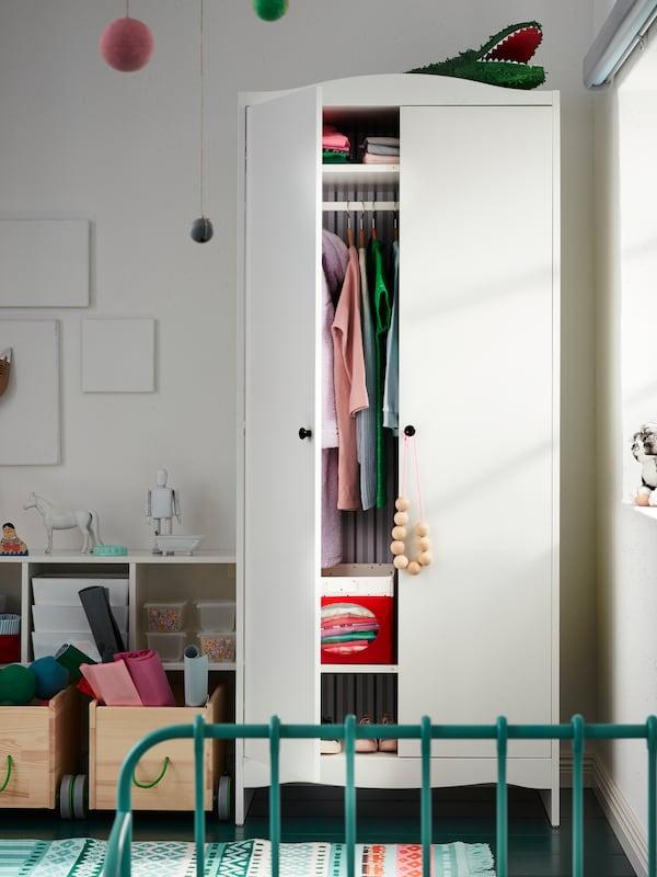 Cameră de copii cu dulap de haine, o ușă a acestuia fiind deschisă. În interior se află cutii și haine împăturite sau agățate.