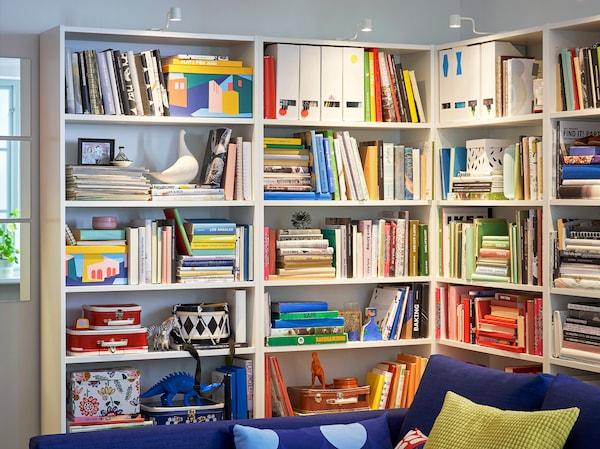 Libreria BILLY con ripiani regolabili nell'angolo di un soggiorno, piena di libri, foto e oggetti decorativi - IKEA