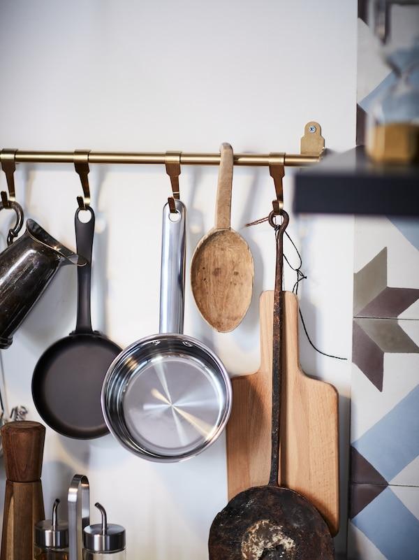 سكة تعليق مطبخ معلق عليها قدور ولوح تقطيع خشبي.