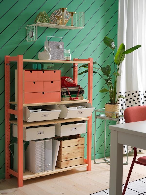 Une salle à manger avec une étagère IVAR avec des tiroirs blancs, une étagère murale blanche, des rideaux blancs et un piédestal verte.