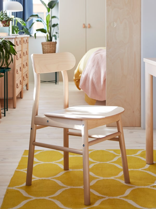 Une chaise en bouleau sur un tapis jaune. Une commode en bouleau et des plantes vertes dans une pièce à l'arrière-plan.