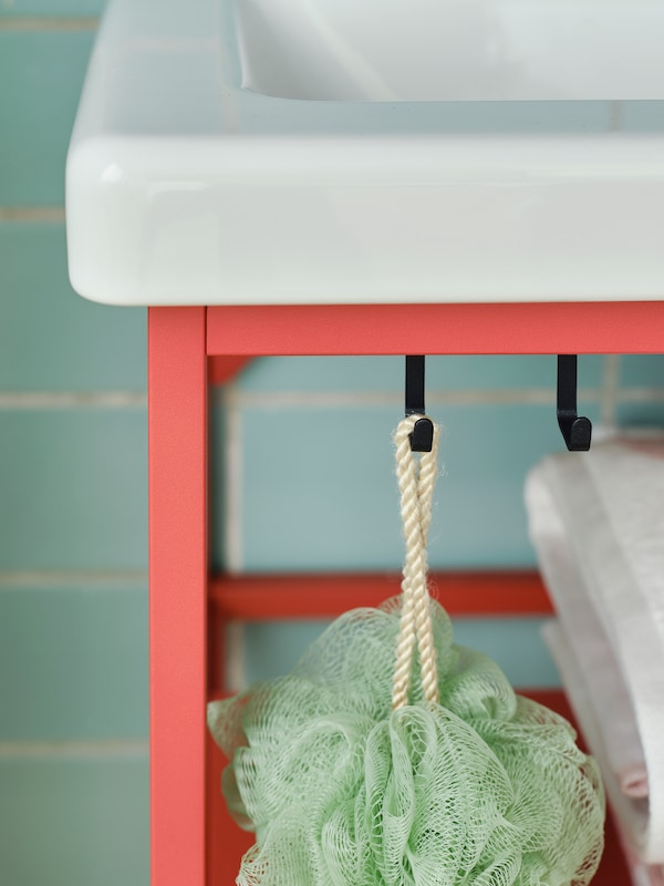 A close-up of the black hooks on a red-orange ENHET washbasin stand in a bathroom propped with bathroom accessories.