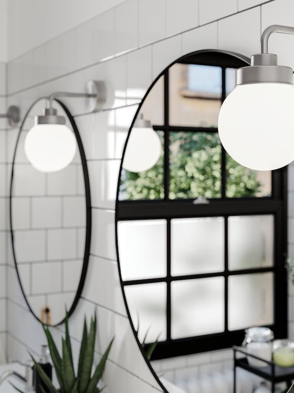 Two round LINDBYN mirrors side by side on a white tiled wall, reflecting a window with greenery outside, plus wall lamps.