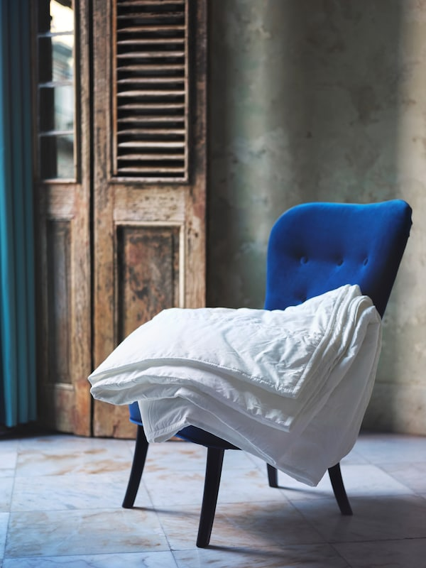 A blue easy chair, with a STJÄRNSTARR duvet folded on top, stands on a tiled floor in front of an open wooden door.