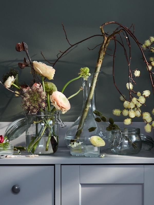Divers arrangements floraux dans des vases, incluant une branche dans une carafe STORSINT, posés sur un buffet HAUGA gris.
