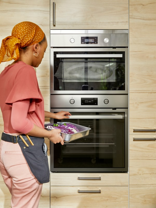 A woman wearing a head-scarf and utility belt placing a tray of food into an oven in a kitchen with door fronts in pale wood.