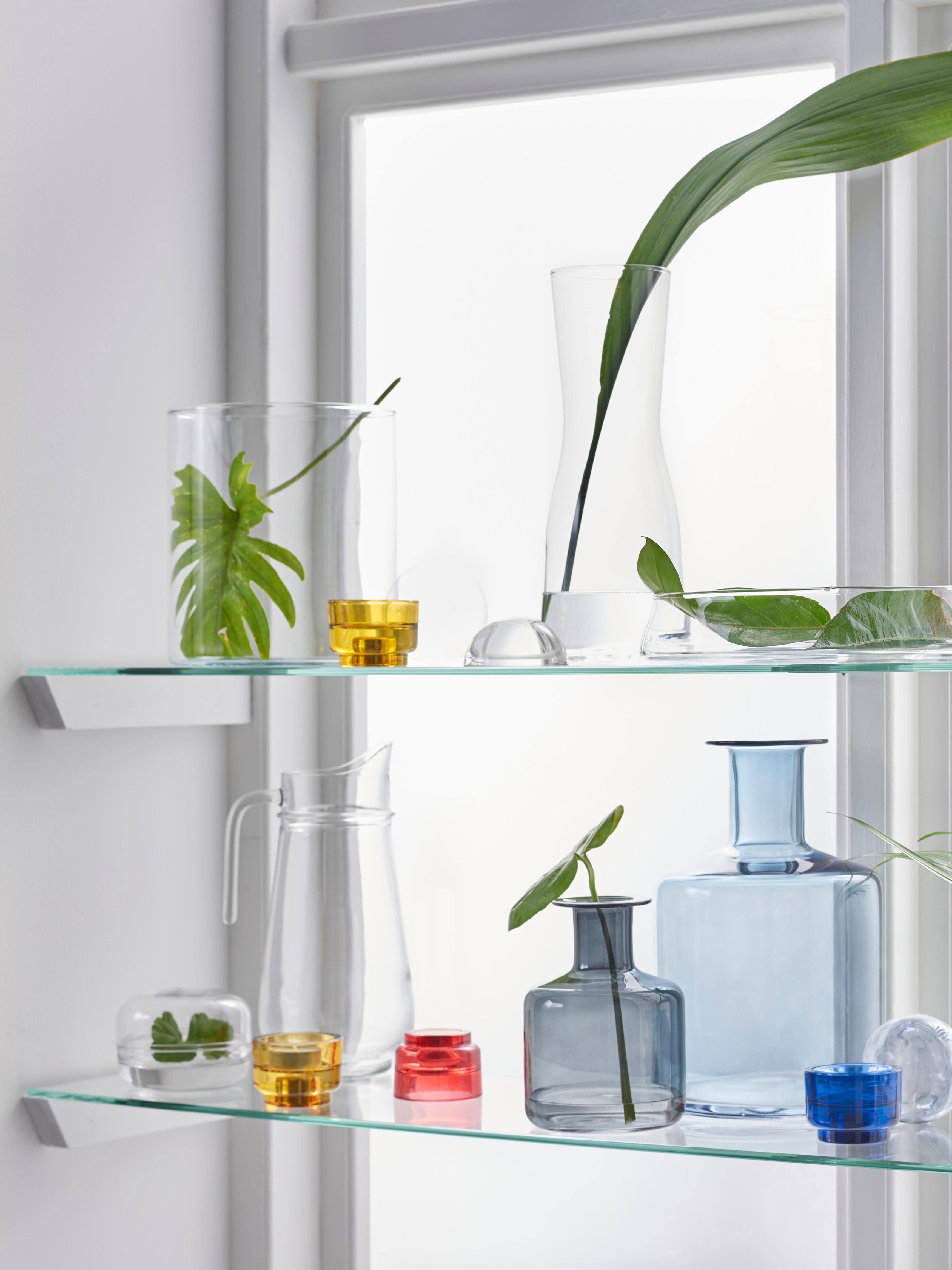 Siva PEPPARKORN staklena vaza od puhanog stakla na sunčanom prozoru pokraj TILLBRINGARE vrča te CYLINDER i TIDVATTEN staklenih vaza.