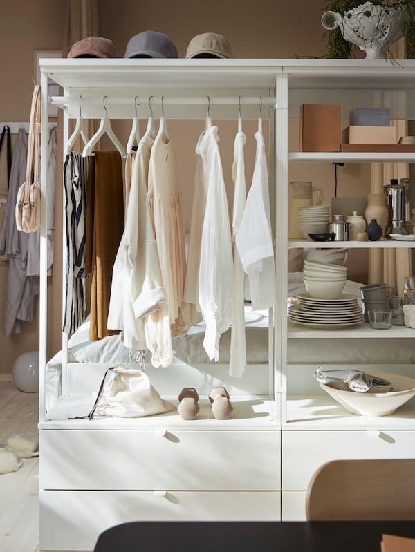 Dulap deschis cu sertare, rafturi și o șină. Haine pe umerașe albe și accesorii decorative pe rafturi.