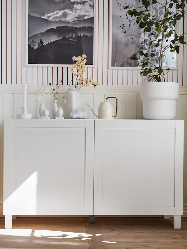 White storage with doors, white plant pots on the top, with other decorations and items, plus pictures behind.