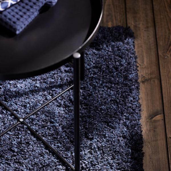 Et GLADOM bakkebord  står på et mørkeblåt VOLLERSLEV tæppe med lang luv, der ligger på et mørkt trægulv.