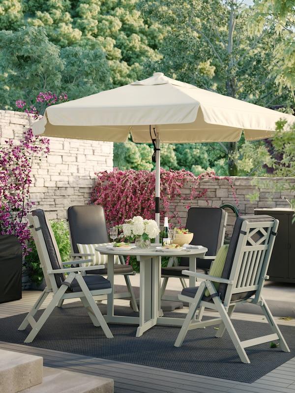 Et havemøbelsæt dækket op til frokost med en beige parasol og fire liggestole med puder stående på et tæppe på en terrasse.