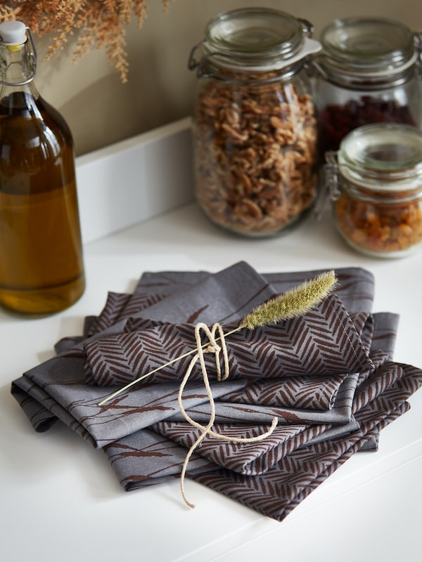 A stack of folded grey HÖSTKVÄLL napkins sit on a sideboard. One napkin is tied with twine and decorated with a dried flower.