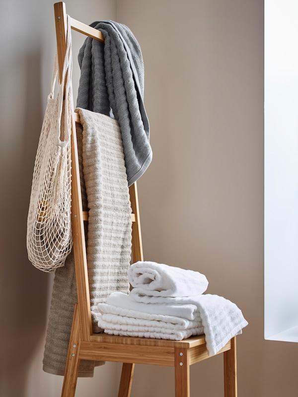 Un scaun cu bară pentru prosoape RÅGRUND cu prosoape și o plasă agățate pe partea din spate și prosoape împăturite așezate pe scaun.