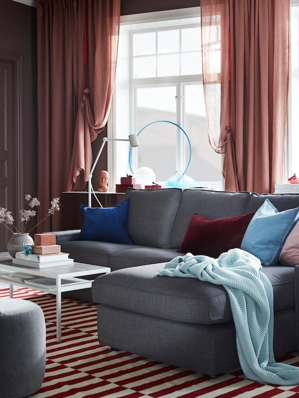 غرفة جلوس تضم صوفا بلون رمادي داكن وطاولة قهوة NYBODA مع سطح يُمكن عكسه: حيث الوجه الأسود في الأعلى.