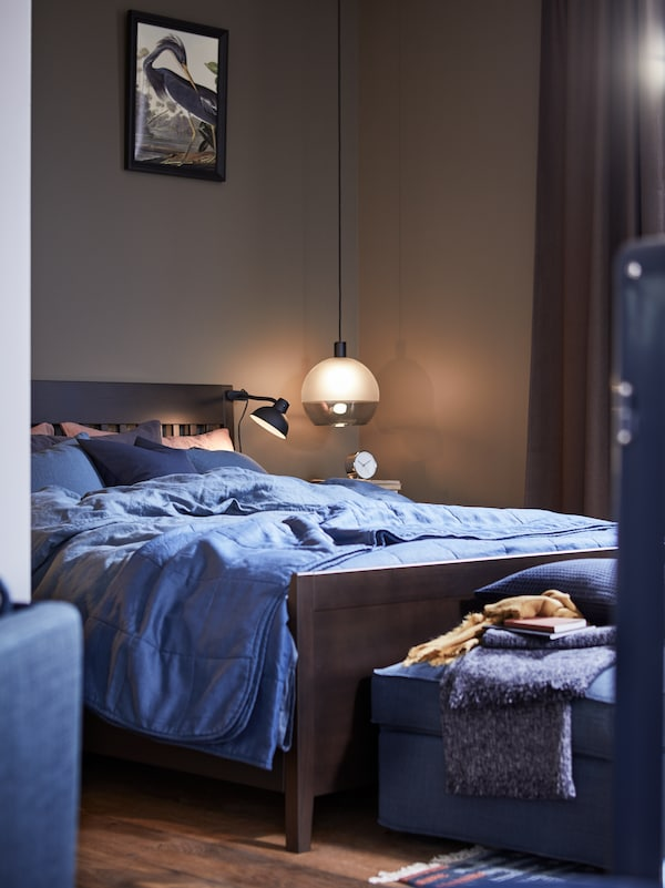 large bedroom with pendent lamp in one corner, blue bedding with a dark wood frame
