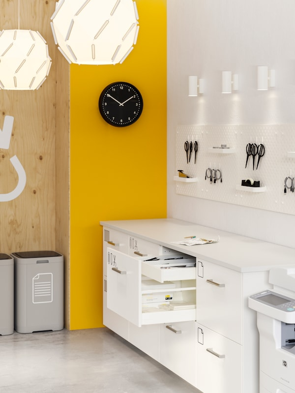 An office with yellow and white walls, white storage with some drawers open, pegboards on the wall with various items.