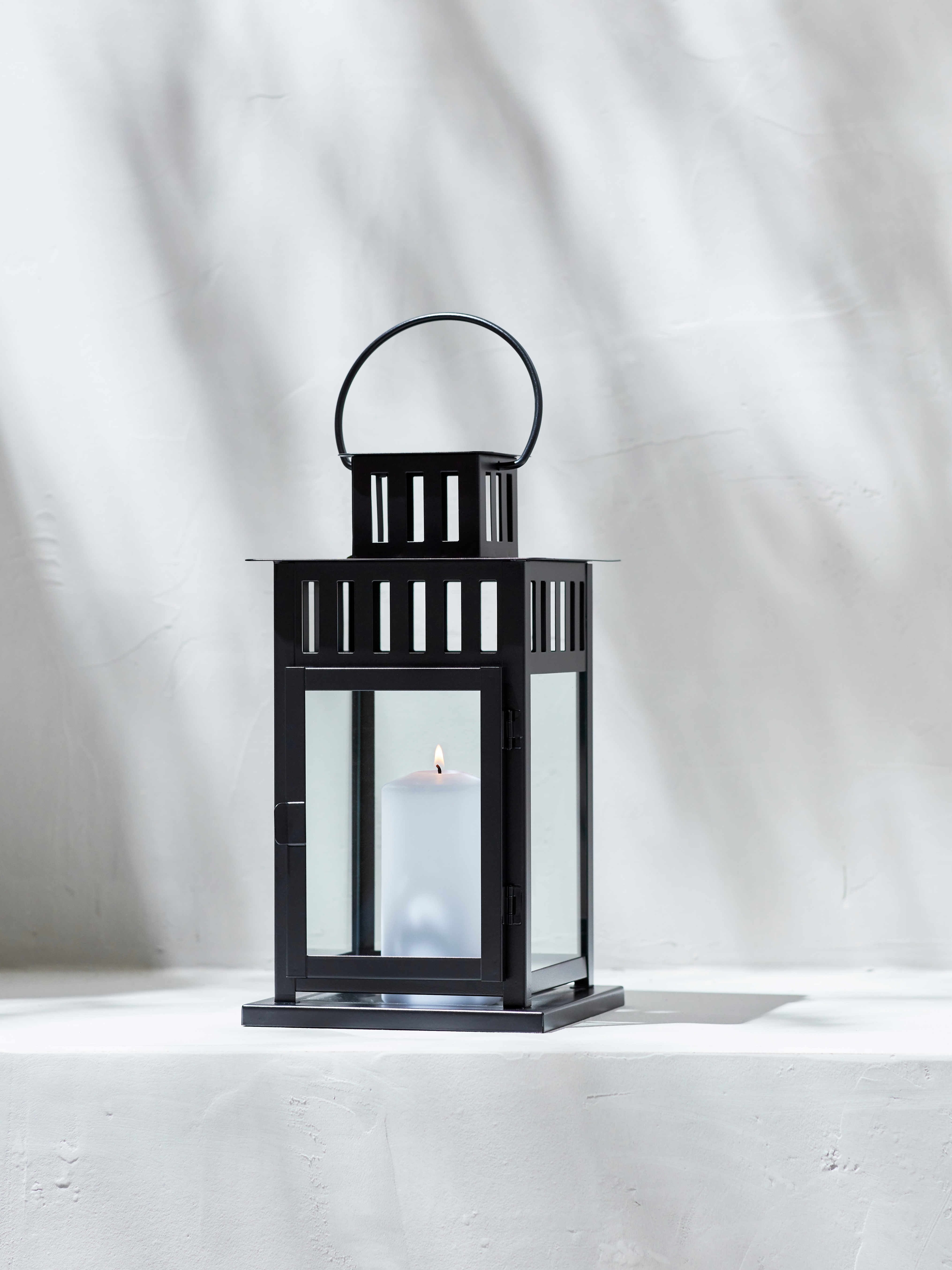 A black, steel and glass BORRBY indoor/outdoor lantern holds a lit, white block candle. It is placed alone on a shaded step.