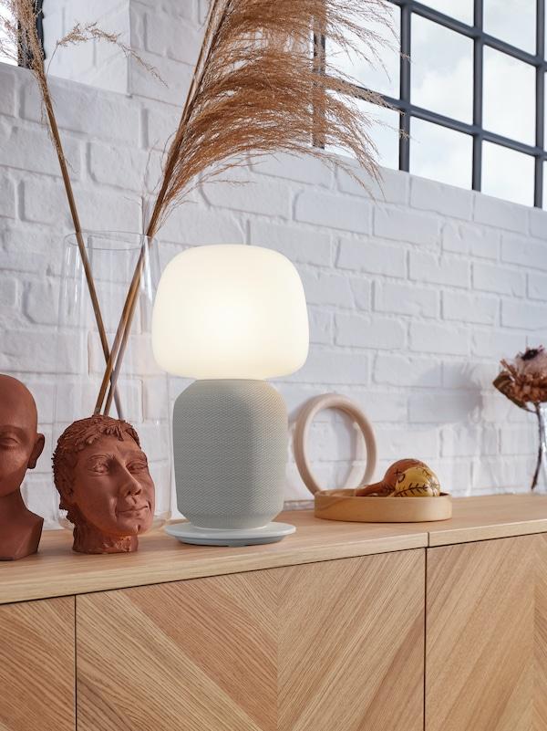 Kombinasi storan dengan pintu, kaki lampu pembesar suara dengan WiFi berwarna putih dan terendak lampu kaca berwarna putih, objek-objek hiasan.