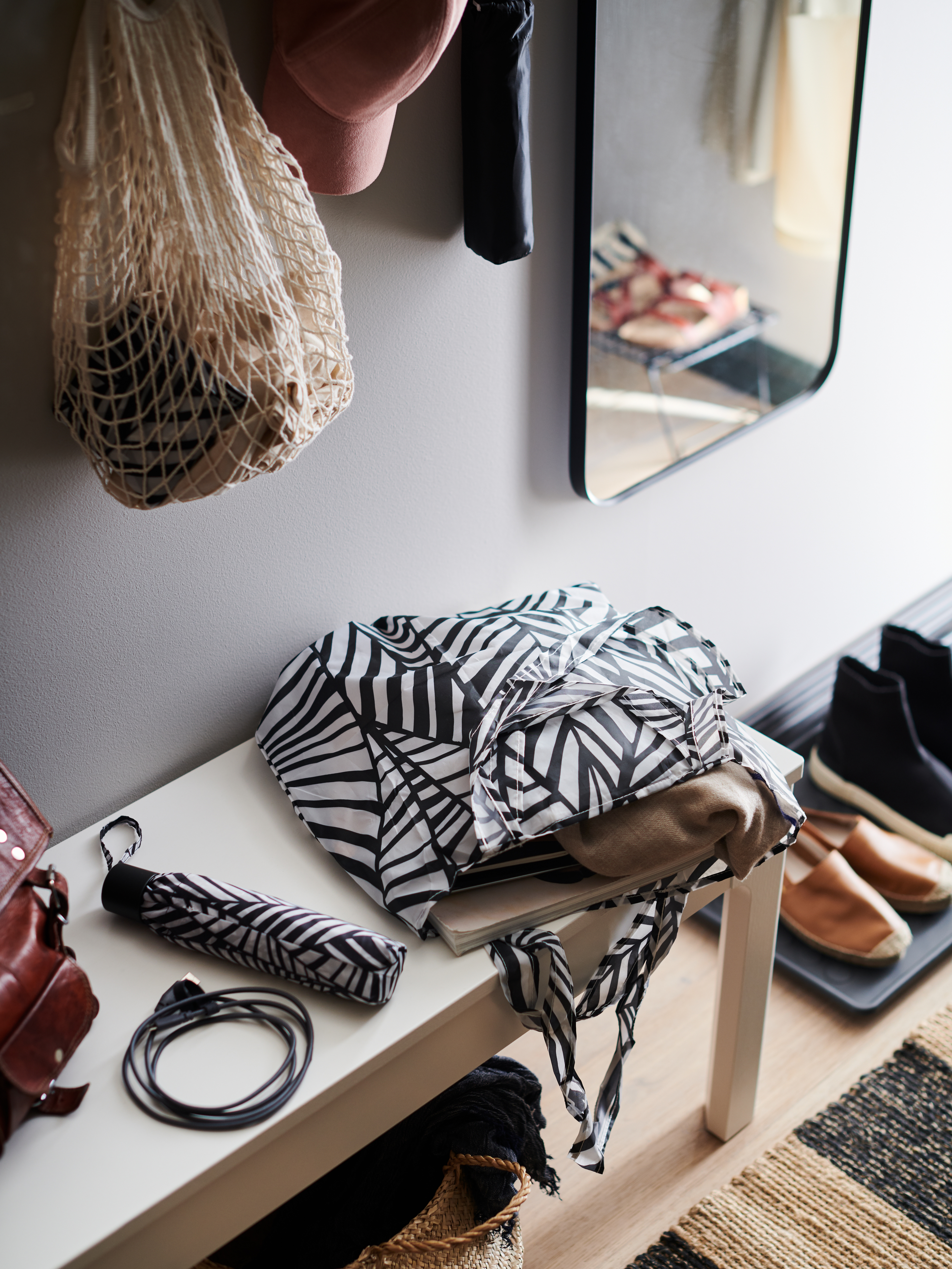A hallway with a mirror, shoes on a mat, and a white bench with a SKYNKE bag, a KNALLA umbrella and a LILLHULT USB cord.