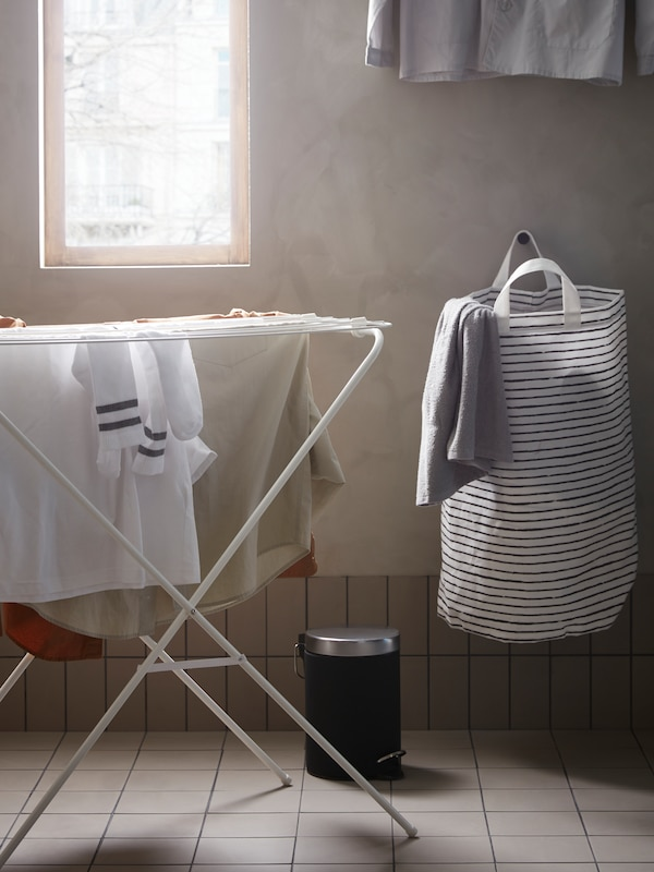 A JÄLL drying rack with clothes on it sits under a window beside an EKOLN waste bin and a KLUNKA laundry bag on the wall.