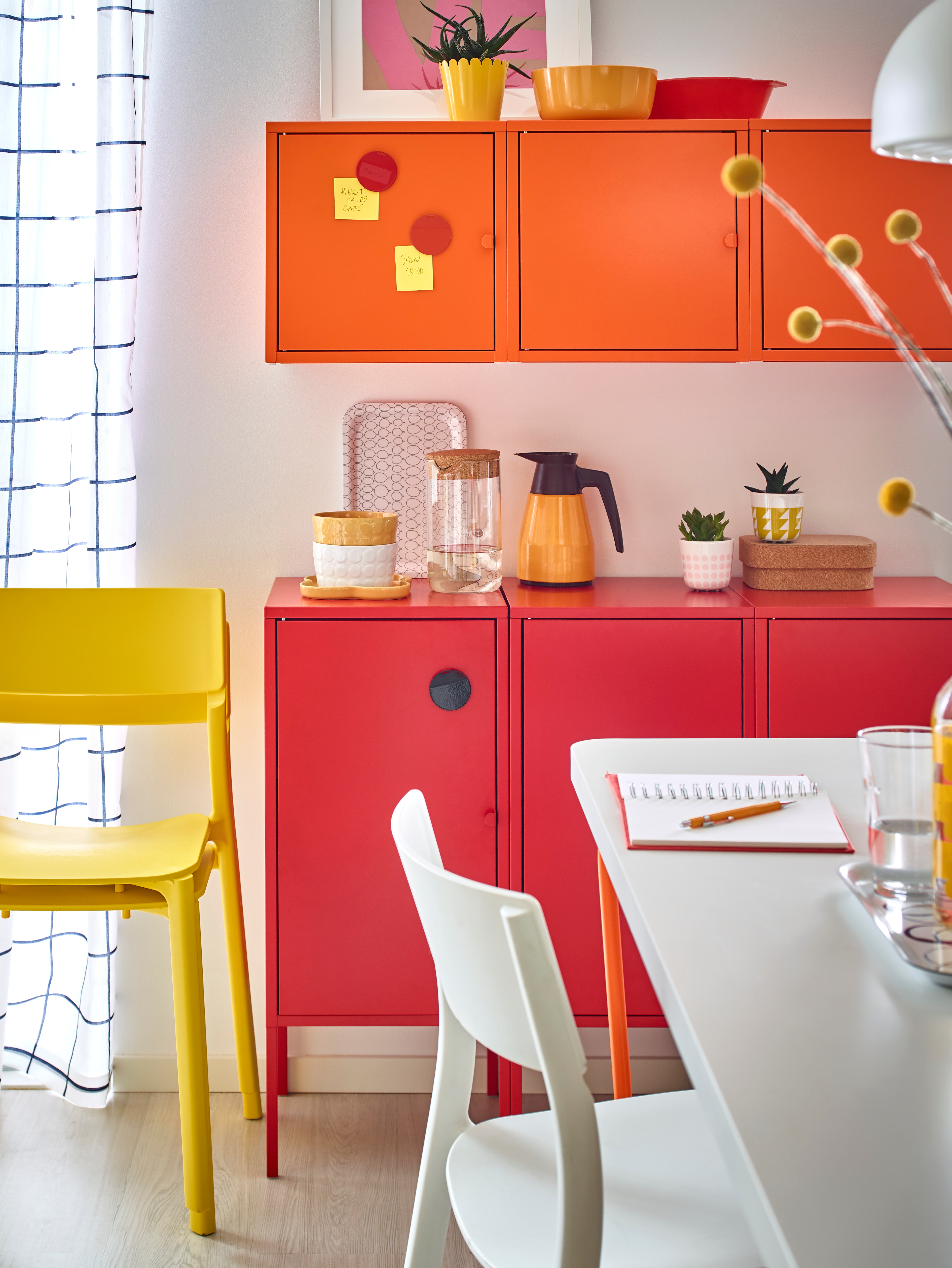 A row of metal/red LIXHULT cabinets has a carafe and tea pot on it, below wall-mounted orange cabinets in a dining area.