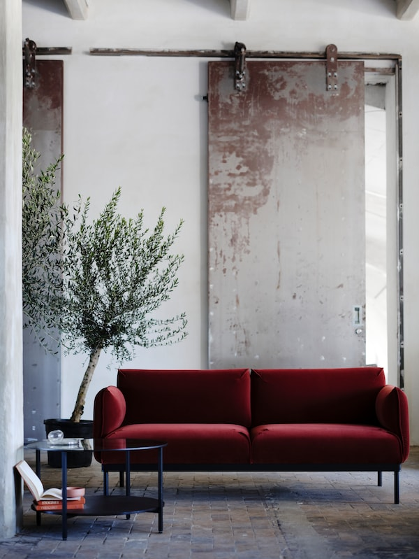 Egy ipari stílusú szoba piros-barna ÄPPLARYD kanapéval, egy VITTSJÖ üveg dohányzóasztallal és egy cserepes fával.