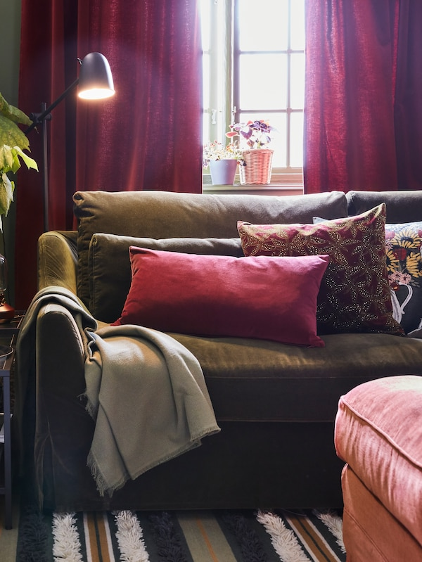 An olive-green sofa with cushions in different colors, a striped rug, a light red footstool and a black floor lamp.