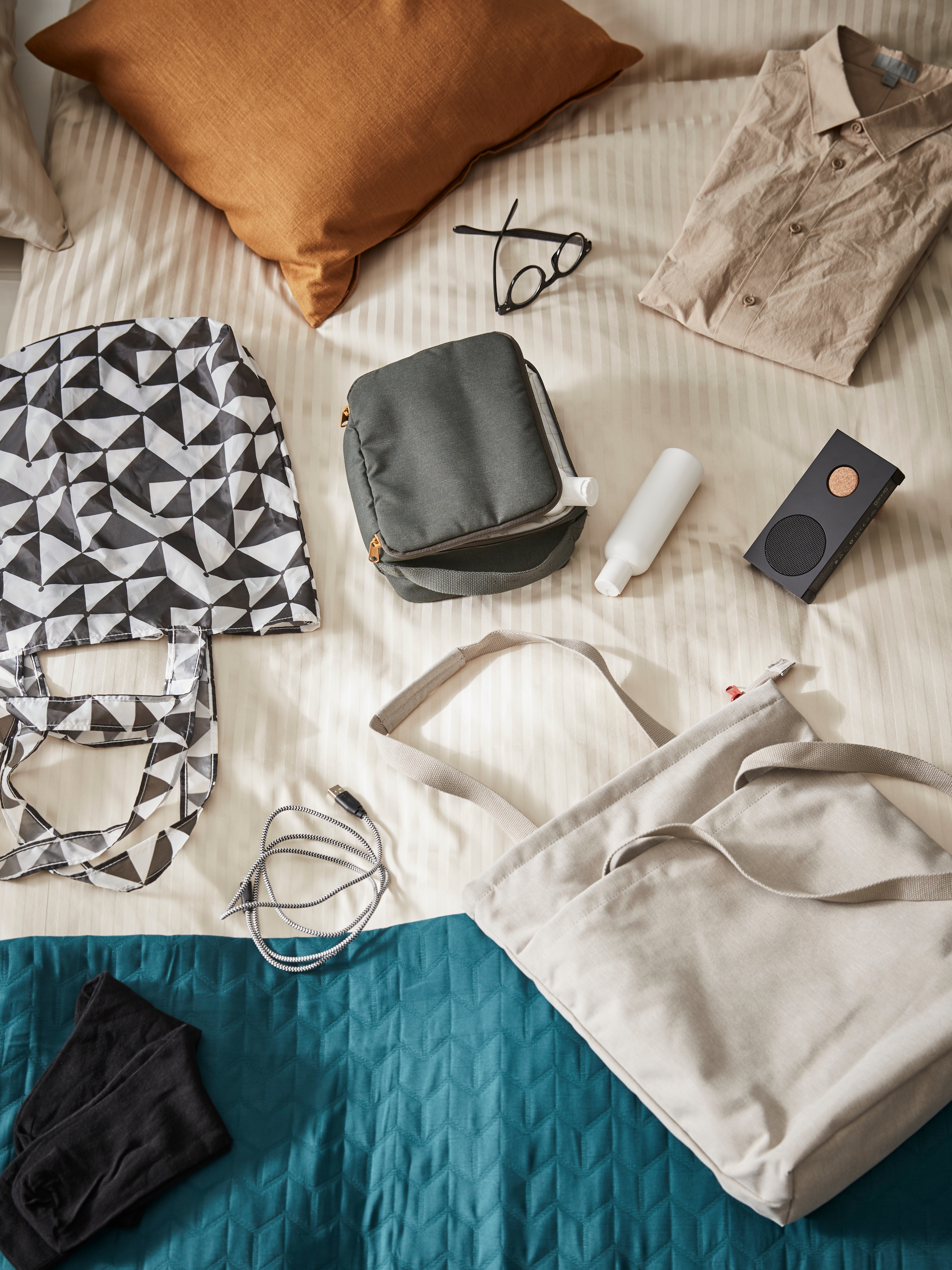 DRÖMSÄCK travel bags lying on a bed next to a tote bag, a USB cable, a pair of glasses, a shirt and a portable speaker.