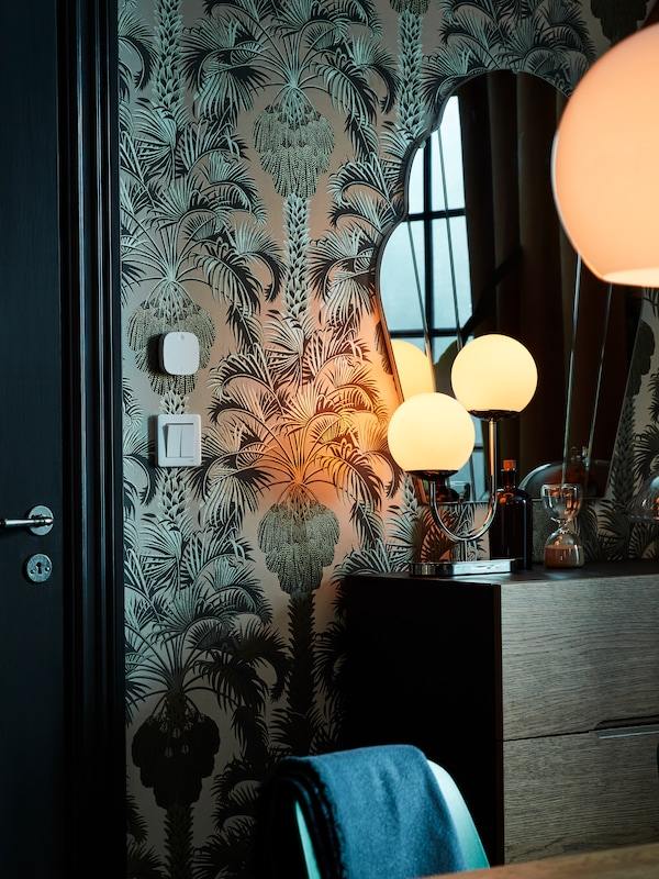 De STYRBAR afstandsbediening van roestvrij staal bevestigd aan een muur met print, met een ladekast tegen de muur en lampen die aanstaan.