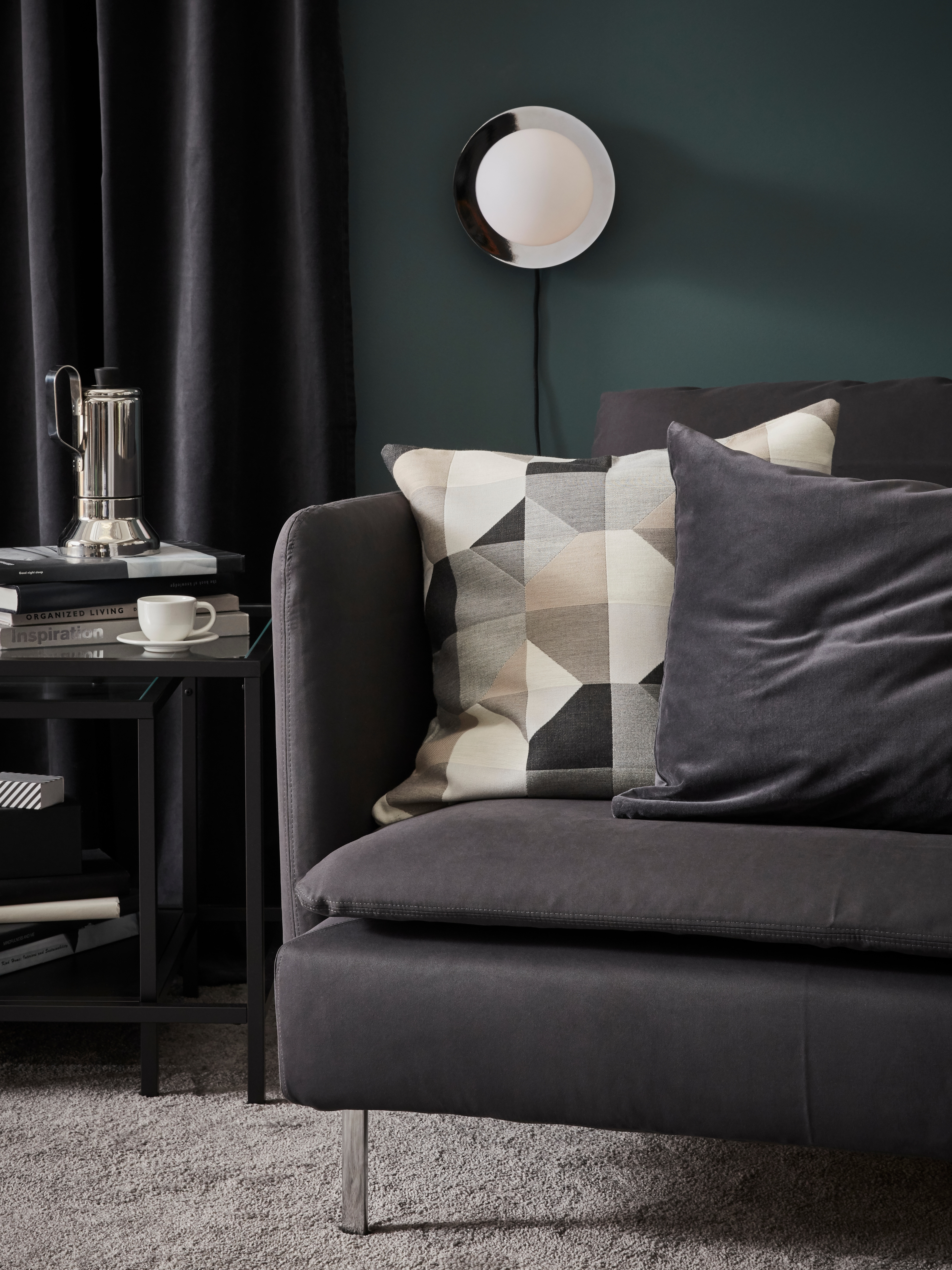 A SIMRISHAMN wall lamp behind a grey sofa with two cushions in neutral tones and a side table with coffee pot and cup.