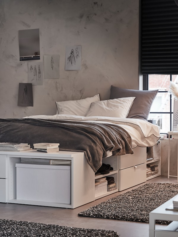 A bedroom where a PLATSA bed with 4 drawers with white and grey bed linen and a TRATTVIVA bedspread sits near a window.