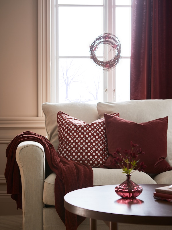 A living room with red textiles, including a throw and two cushion covers.