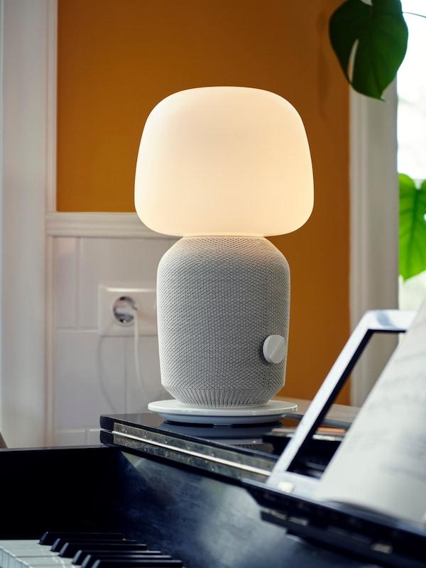 Una lampada da tavolo con cassa Wi-Fi SYMFONISK appoggiata su un pianoforte; sullo sfondo una parete bianca e arancione e una pianta.