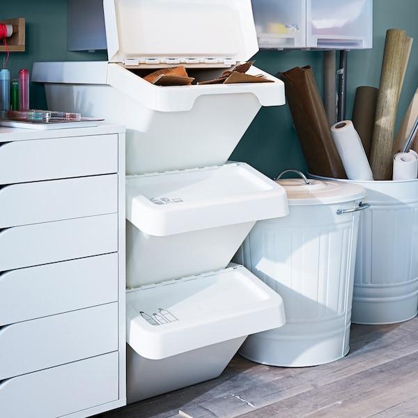 O unitate sertar ALEX cu rotile lângă trei cutii de sortare a deșeurilor SORTERA stivuite și două coșuri KNODD cu capac, toate în alb.