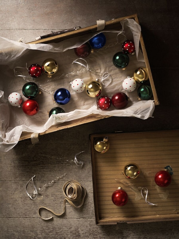 A selection of shiny baubles in blue, white, red, green and gold spread inside the lid of a brown cardboard box.