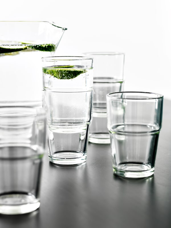 Several REKO clear glasses, some are stacked and sparkling water is being poured into one glass with a slice of lime inside.