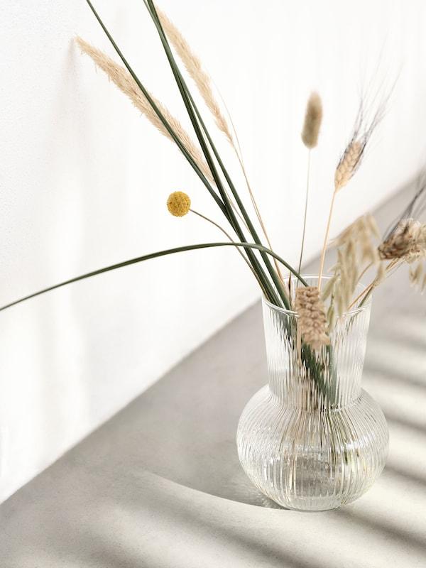 Przezroczysty szklany wazon PÅDRAG wypełniony prostym bukietem suszonych kwiatów i traw.