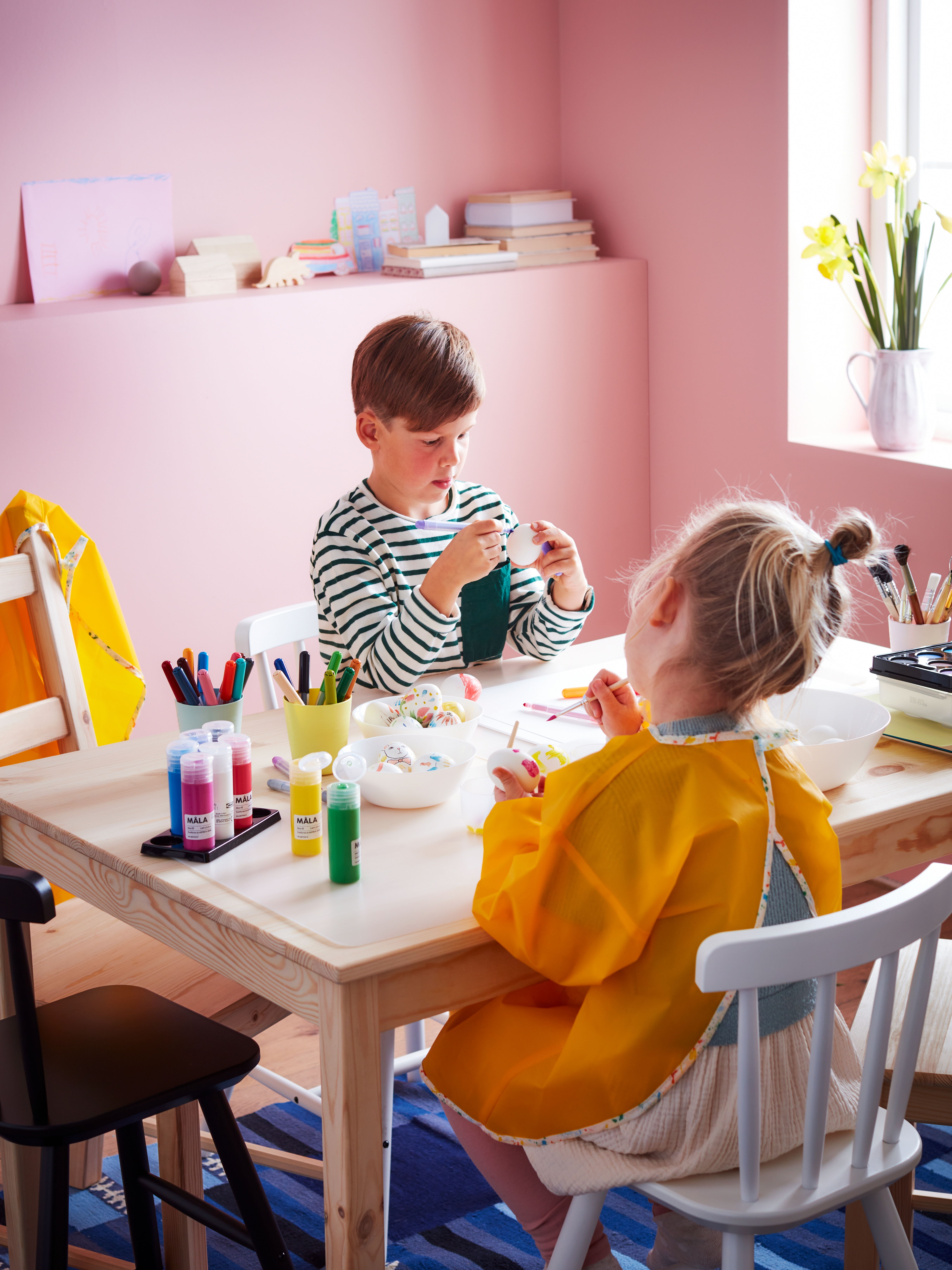 Two children sit at a low table, engrossed in colouring eggs. The table is filled with eggs and MÅLA felt-tip pens and paint.