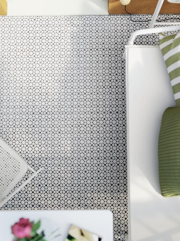 Hellgrauer Bodenbelag, ein weisses Sofa, ein Klappstuhl und Dekokissen in Grün und Weiss.