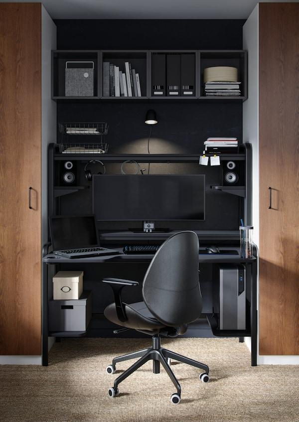 Une chaise pivotante noire sous un bureau noir encastré.