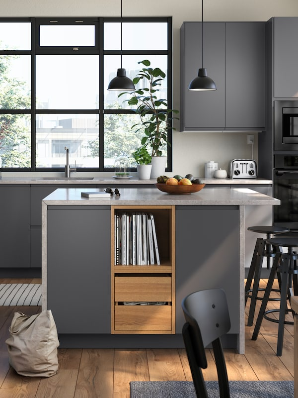 A sleek kitchen in grey with a kitchen island featuring a wraparound grey quartz worktop and two black pendant lamps.