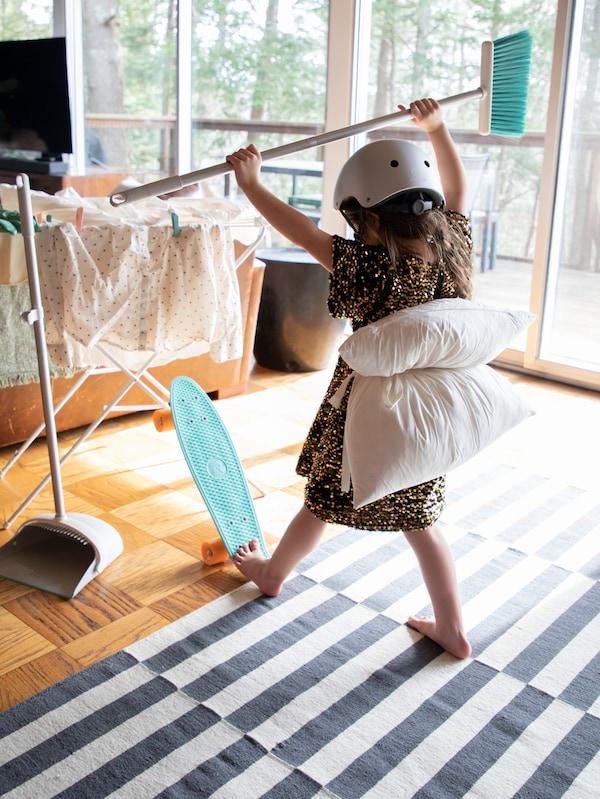 Ein Kind trägt einen Helm und hat sich ein FJÄDRAR Kissen auf den Rücken gebunden. Mit einem Fuss steht es auf einem Skateboard und in der Hand hält es einen Besen.